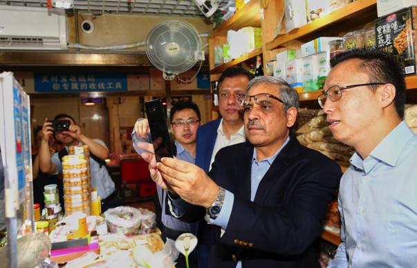 图说:2018年7月25日,巴基斯坦央行行长借用蚂蚁金服掌门人井贤栋的支付宝尝试扫码买一包葡萄干